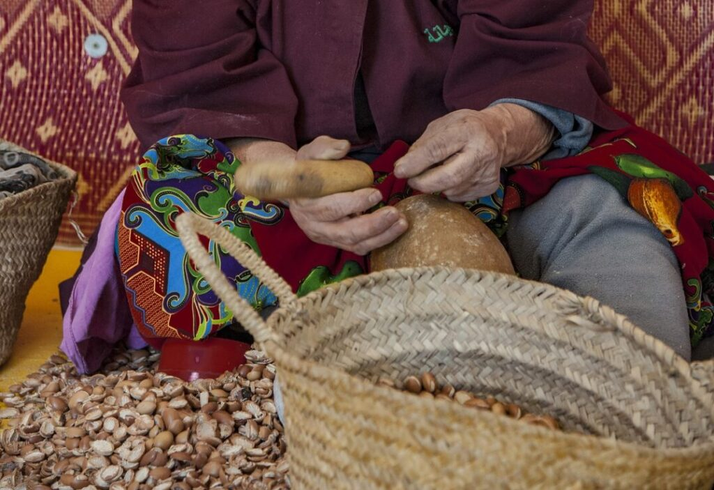 woman cracking argan fruits