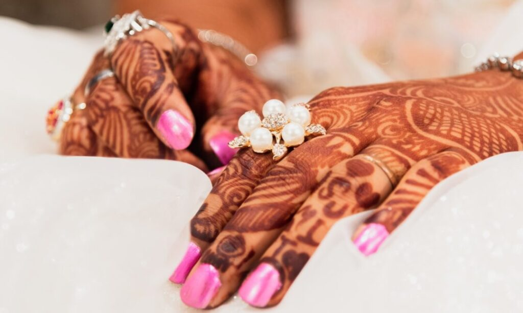 hands with henna and pink nails